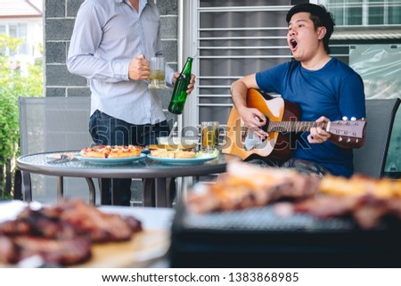 Group of friends Two young man enjoying grilled meat and play guitar with raise a glass of beer to celebrate the holiday festival happy drinking beer outdoors and enjoyment at home. #1383868985