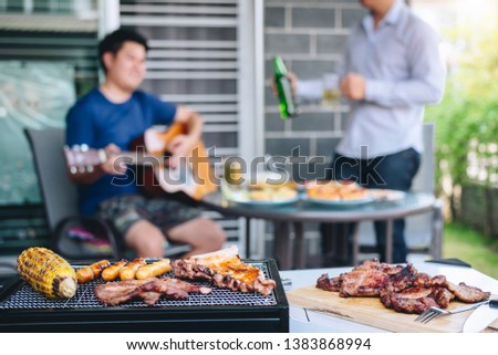 Group of friends Two young man enjoying grilled meat and play guitar with raise a glass of beer to celebrate the holiday festival happy drinking beer outdoors and enjoyment at home. #1383868994