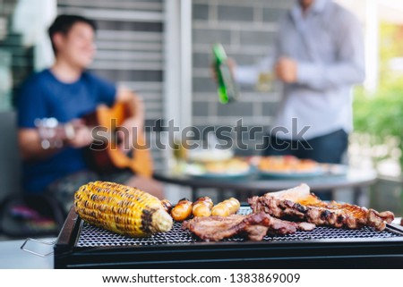 Group of friends Two young man enjoying grilled meat and play guitar with raise a glass of beer to celebrate the holiday festival happy drinking beer outdoors and enjoyment at home. #1383869009