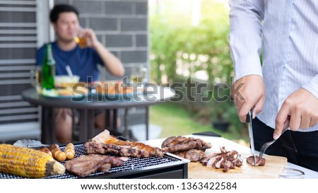 Group of friends Two young man enjoying grilled meat and raise a glass of beer to celebrate the holiday festival happy drinking beer outdoors and enjoyment at home.