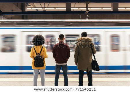Group of friends waiting the train in the platform of subway station. Public transport concept. stock photo