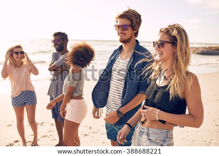 Group of friends walking along a beach at summertime. Happy young people enjoying a day at beach.