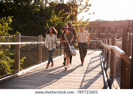 Group Of Friends Walking Along Bridge In Urban Setting
