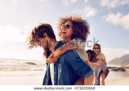 Group of friends walking along the beach, with men giving piggyback ride to girlfriends. Happy young friends enjoying a day at beach.