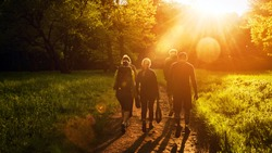 Group of friends walking with backpacks in sunset from back. Adventure, travel, tourism, hike and people friendship concept. Sports activity