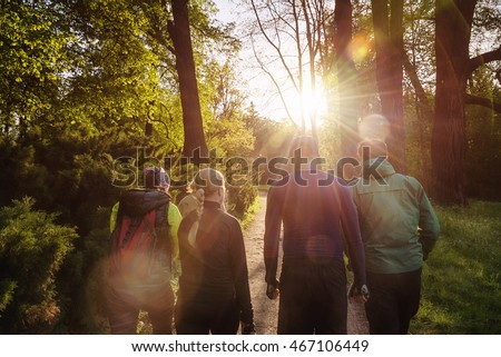 Group of friends walking with backpacks in sunset from back. Adventure, travel, tourism, hike and people friendship concept #467106449