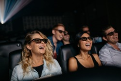 Group of friends watching 3d movie and laughing in cinema. Happy young men and women watching 3d film in theater.