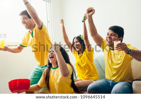 Group of friends watching soccer game on television, celebrating goal and screaming #1096645514