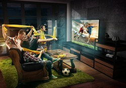 Group of friends watching TV, football match, sport together. Emotional men and women cheering for favourite team, look on goal and fighting for ball. Concept of friendship, leisure activity, emotions