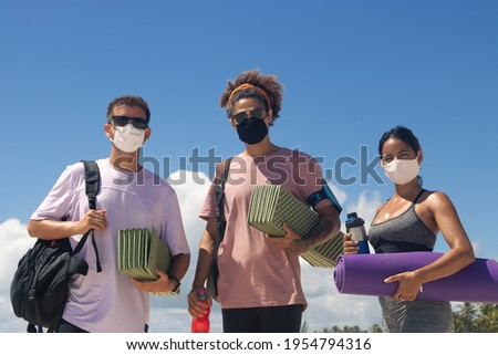Group of friends wearing masks dressed in sportswear holding sports equipment ready to train on the beach. Сток-фото ©