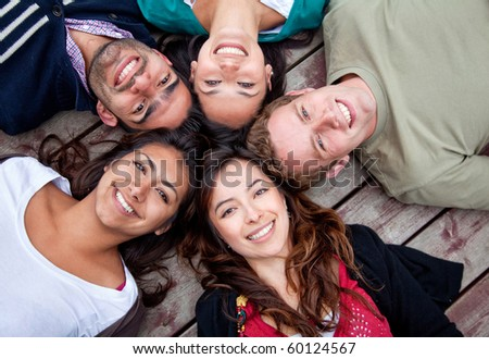 Group of friends with their heads together in a circle outdoors #60124567
