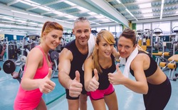 Group of friends with thumbs up smiling on a fitness center after hard training day