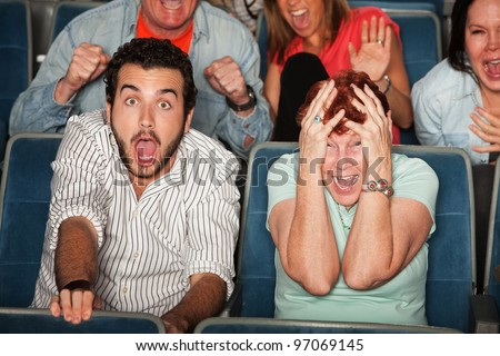 Group of frightened people in a theater
