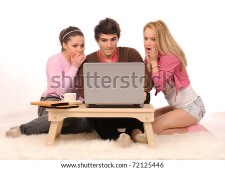 Group of frightened young people having fun with laptop on white background.