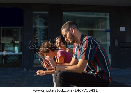Group of gadget users sitting on bench outdoors. Side view of men and woman using smartphones and tablets. Digital technology concept #1467755411