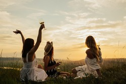 Group of girl friends with wine glasses chilling on picnic blanket at summer day. They enjoying amazing sunset. Copy space.