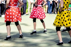 Group of girls dancing in fashionable costumes. Dance group perform show in bright polka dots dresses. Retro style, vintage, fashion and outdoors concert concept