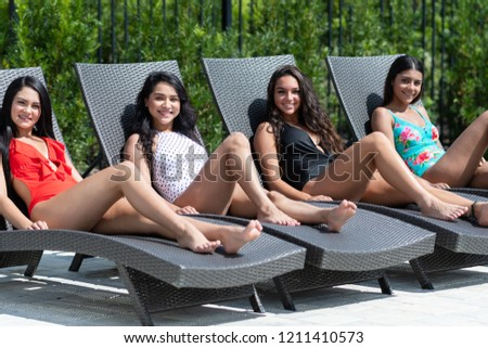 Group of girls laying out in the sun to get a tan #1211410573