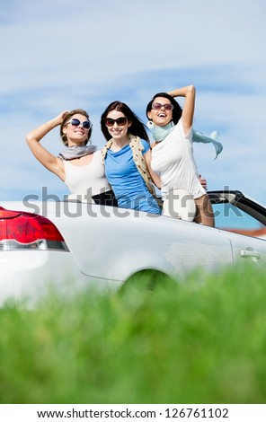 Group of girls stands in the auto with hands up. Happy journey of joyful teenagers