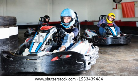 Group of glad cheerful positive smiling people driving go-carts at racing track #1553439464