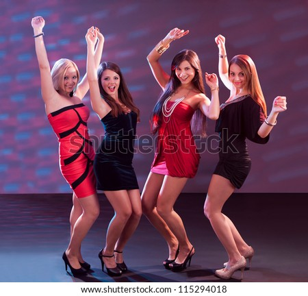 Group of glamorous young women in evening attire dancing together at a nightclub or disco
