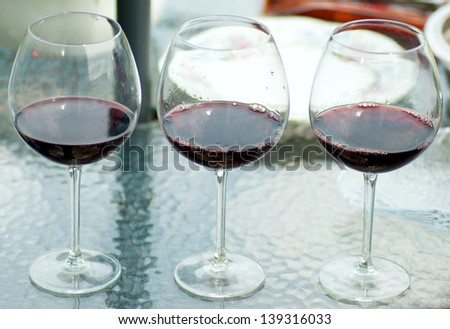 group of glasses with wine on a glass table.