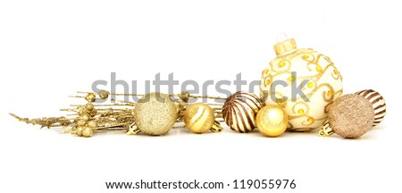 Group of gold Christmas baubles and branches arranged as a border over white