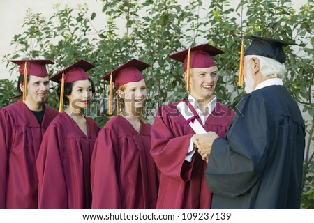 Group of graduates in line collecting certificate from male dean