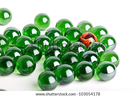Group of green glass marbles with one orange marble in a concept of uniqueness or individuality
