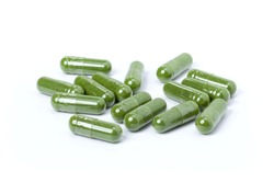Group of green herbal medicine powder capsules isolated on white background.