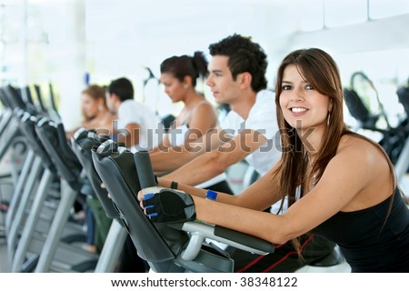 Group of gym people exercising on cardio machines