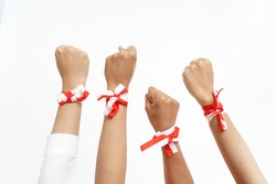 group of hand put together wearing indonesian red and white ribbon on a wrist. unity concept