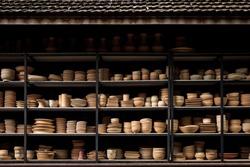 Group of handcraft ceramic kitchenwares arranged on shelve in warehouse pottery workshop studio.