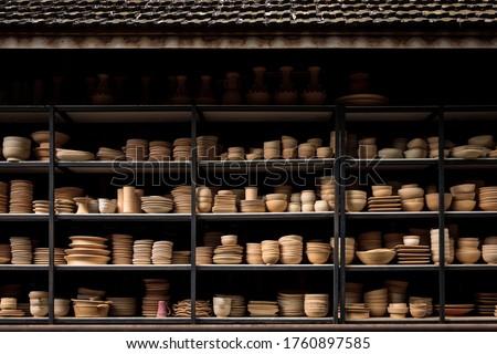 Group of handcraft ceramic kitchenwares arranged on shelve in warehouse pottery workshop studio. Сток-фото ©