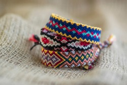 Group of handmade homemade colorful natural woven bracelets of friendship isolated on jute background material background
