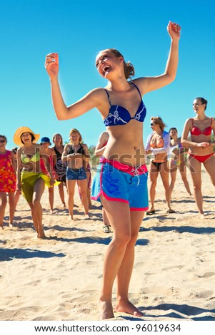 Group of happy active girls dancing at the beach