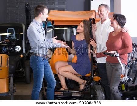Group of happy adult friends selecting grand tour electric at rental store. Selective focus