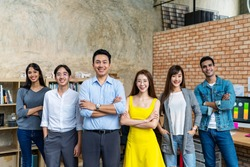 Group of happy asian employee are standing and looking at camera with feeling confident at workplace company. Portait of Asian creative team posing in workspace.