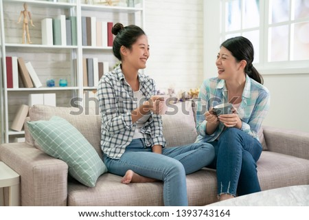 group of happy asian female friends talking and laughing loud holding drinks sitting on sofa in the living room at home. young girls sisters gossip having fun on couch with tea cups indoors apartment