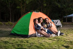 Group of happy Asian Indian pretty girls camping by the tent. Outdoor activity, adventure travel, or holiday vacation concept