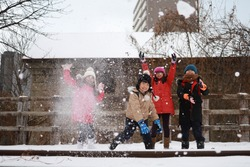 Group of happy Asian kids boys and girls having fun outdoor, throwing snow in the air together. Winter holiday.