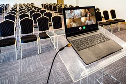 Group of happy business coworkers having video call over laptop in empty conference hall.