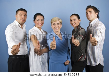 Group of happy business group giving thumbs up and smiling isolated on blue background