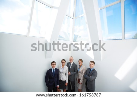 Group of happy business partners looking at camera in office