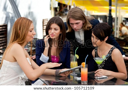 Group of happy business partners or friends enjoy colorful cocktails and talk outdoors. They use tablet and smart phones.