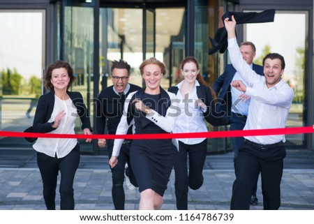 Group of happy business people running from office building crossing red ribbon finish line #1164786739