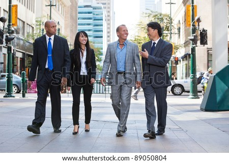 Group of happy business people walking together on street - stock photo
