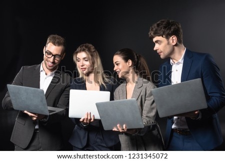 group of happy business people working with laptops together isolated on black #1231345072