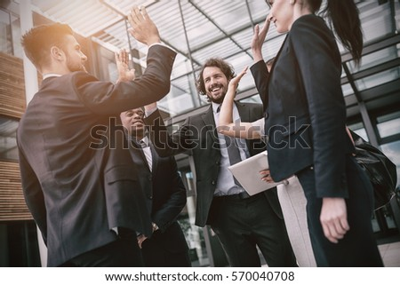 Group of happy businesspeople giving high five to each other in office premises #570040708