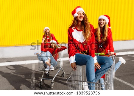 Group of happy cheerful young women in christmas sweaters and santa claus hats walking down city street riding shopping trolleys near shopping mall